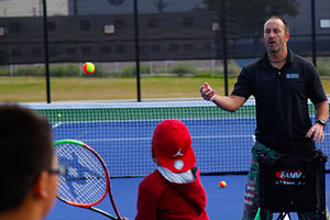 Tobias Ortegon, tennis coordinator for Denver Parks and Recreation leads Greenlee students through practice drills. PHOTO: Trevor Davis