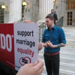 A sign endorsing marriage equality is held while Matt Spencer of the grassroots organization Restore Humanity speaks to a crowd member. Photo by Angela Jackson.