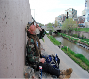 A homeless man sits across the street from MSU Denver's Science Building. [Photo: Chris Bjork]