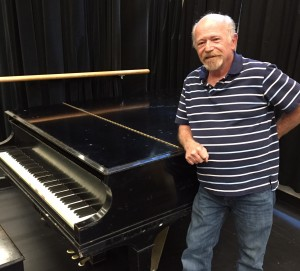 Chuck Hinshaw leans on a piano at Metropolitan State University of Denver on Thursday, Sept. 17, 2015. Hinshaw's lifelong career has been refinishing pianos and furniture. (MSU Denver/Timothy Carroll)