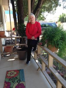 Liz sits on the porch of her house. [Photo: Debbie Rose