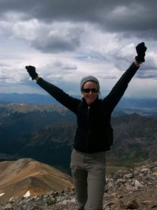 Paula Severseike standing on top of a Colorado's 14 teeters 14,000-foot mountain for her 50th birthday,