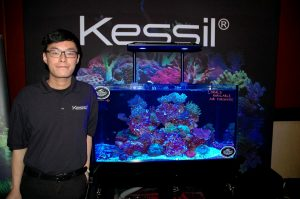 Franco Chan explains to guests that Kessil makes a lot of lights. They also provided lights for the show, seen in tanks throughout ReefStock. [Photo: Duane Hirschfeld]