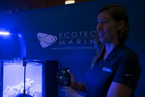 Nicole Helgason, 31, demonstrates how to use Ecotech Marine's MP40 pump to create flow in an aquarium on Feb. 25. It's really important for corals to have light, flow and filtration. [Photo: Kavann Tok]